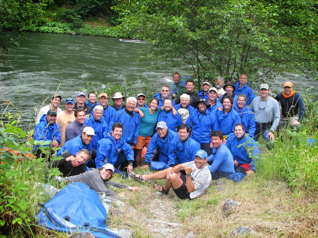 Large corporate group gathers for photo on whitewater rafting trip